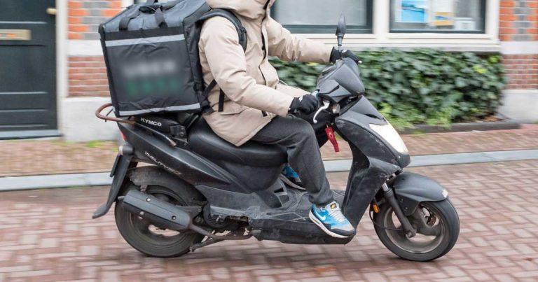Homem a conduzir moto de entrega de comida Uber Eats